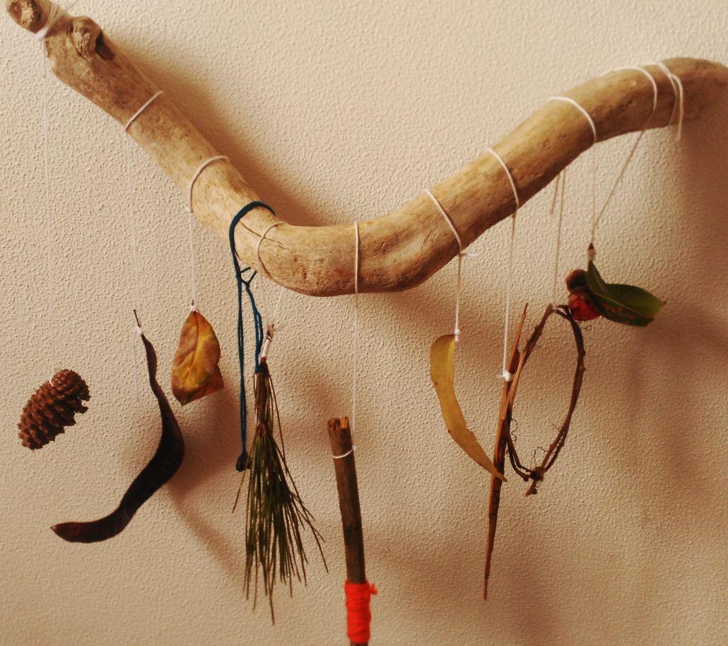 Palo con tesoros naturales colgando. Una piña cerrada, laurel seco, eucalipto, hoja de eucalipto seca, corteza, camelia...